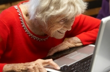 Elderly lady looking over a laptop