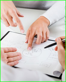 Two people pointing at a project plan on a desk.