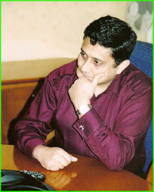 Photograph of Sanjay Morzaria wearing a purple shirt during a conference call