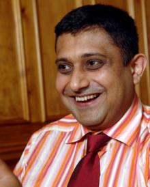 Photograph of Sanjay Morzaria wearing an orange and white stripped shirt.