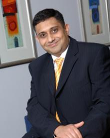Photograph of Sanjay Morzaria wearing a dark suit.