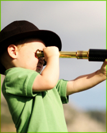 A little boy looking ahead through a telescope